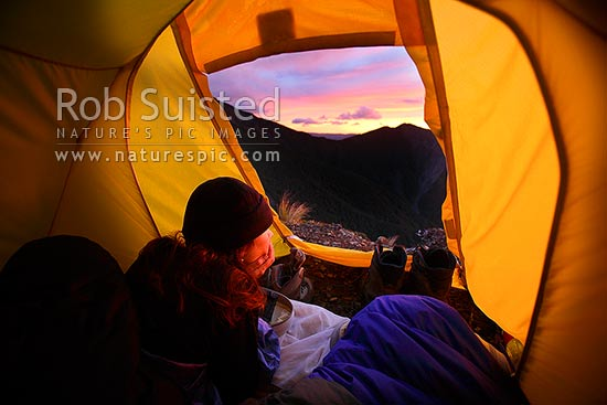 Tramper enjoying the dramatic sunrise through tent door in the Ruahine Range. Alpine tent camping, Ruahine Forest Park, New Zealand (NZ) stock photo.