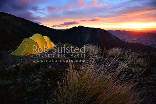 Dramatic sunrise over tent in the Ruahine Range. Alpine tent camping near Sunrise Hut, Ruahine Forest Park, Central Hawke's Bay District, Hawke's Bay Region, New Zealand (NZ) stock photo.