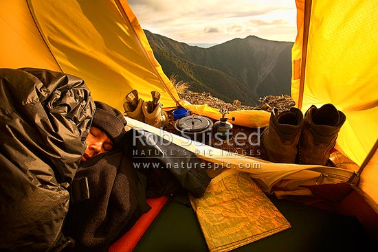 Tramper sleeping during a sunrise in the Ruahine Range. Alpine tent camping in the tussock tops. Map, cooker and boots. Hiking, Ruahine Forest Park, New Zealand (NZ) stock photo.