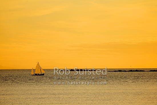 Small sailing ketch yacht in Plimmerton Harbour at twilight. Tokeapapa reef (Grandfather rocks) and South Island (faint) behind, Plimmerton, Porirua City District, Wellington Region, New Zealand (NZ) stock photo.