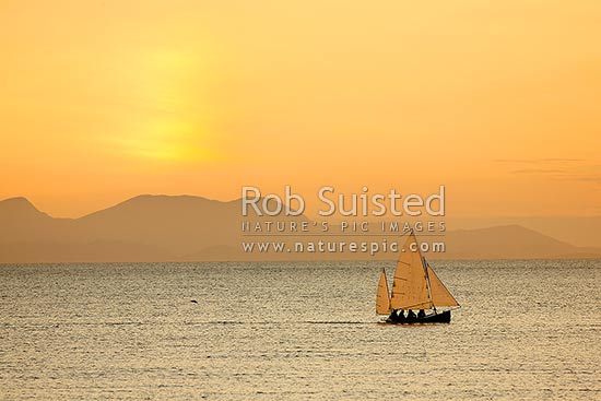 Small sailing ketch yacht in Plimmerton Harbour at twilight. Cook Strait and South Island behind, Plimmerton, Porirua City District, Wellington Region, New Zealand (NZ) stock photo.