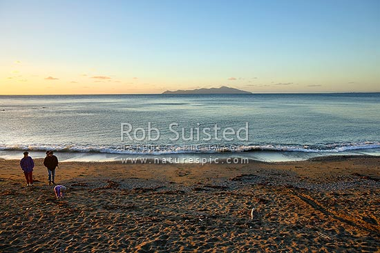 People and family enjoying calm sunset over Pukera Bay Beach and Kapiti Island, Pukerua Bay, Porirua City District, Wellington Region, New Zealand (NZ) stock photo.