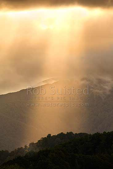 Dramatic clouds and shafts of sun lighting on Tararua foothills and forest ranges. Breaking storm, Carterton, Carterton District, Wellington Region, New Zealand (NZ) stock photo.