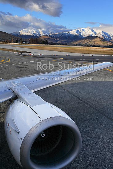 Winter snow on the Crown Range behind Queenstown Airport and Boeing 737 aircraft on tarmac, Queenstown, Queenstown Lakes District, Otago Region, New Zealand (NZ) stock photo.