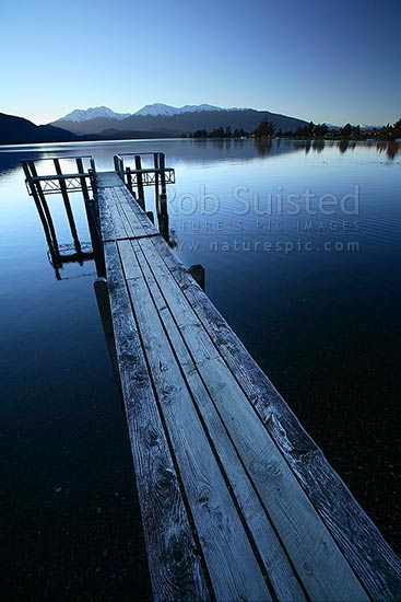 Calm winter twilight reflections on Lake Te Anau and jetty. Snowy Murchison Mountains behind, Te Anau, Southland District, Southland Region, New Zealand (NZ) stock photo.