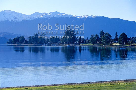 Calm winter on Lake Te Anau and township, with snowy Murchison Mountains behind, Te Anau, Southland District, Southland Region, New Zealand (NZ) stock photo.