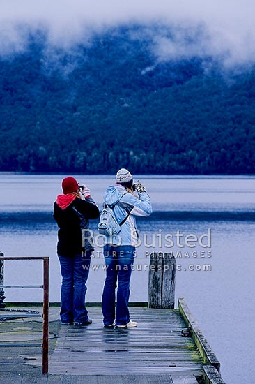 Two woman tourists photographing on a calm moody winter's morning on Lake Te Anau jetty, Te Anau, Southland District, Southland Region, New Zealand (NZ) stock photo.