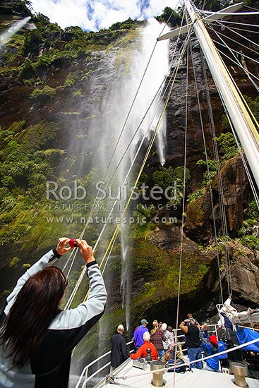 Tourists on deck of cruise boat photographing Fairy Falls Waterfall, Fiordland National Park, Milford Sound, Fiordland National Park, Southland District, Southland Region, New Zealand (NZ) stock photo.