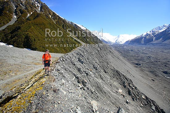 Tramper walking along the lateral moraine of the Tasman Glacier, Tasman Valley.Towards De La Beche ridge. Southern Alps, Aoraki / Mount Cook National Park, MacKenzie District, Canterbury Region, New Zealand (NZ) stock photo.
