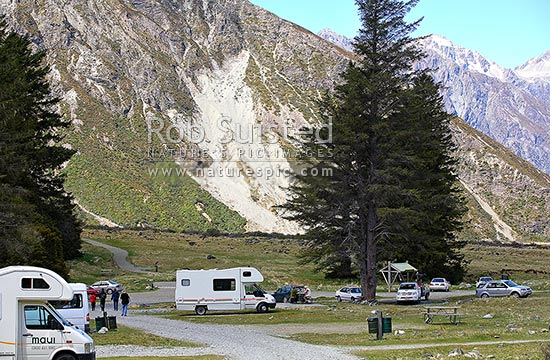 Campervans or motorhomes and vehicles in Department of Conservation (DOC) White hourse campground. Cars and tent camping. People in the distance, Aoraki / Mount Cook National Park, MacKenzie District, Canterbury Region, New Zealand (NZ) stock photo.