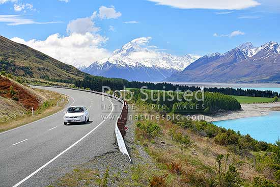 Car on State highway 80, Lake Pukaki with snowy Aoraki / Mount Cook and Southern Alps behind, Aoraki/Mount Cook National Park, MacKenzie District, Canterbury Region, New Zealand (NZ).