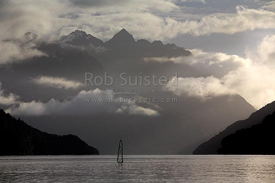 Looking across moody Lake Manapouri to the Cathedral Peaks Range in Kepler Mountains, shrouded in morning mist, from West Arm, Lake Manapouri, Southland District, Southland Region, New Zealand (NZ) stock photo.