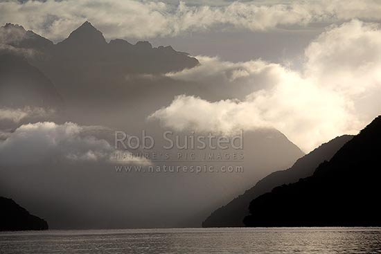 Looking across Lake Manapouri to the Cathedral Peaks Range in Kepler Mountains, shrouded in morning mist, from West Arm. Moody shot, Lake Manapouri, Southland District, Southland Region, New Zealand (NZ) stock photo.