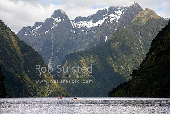 Wilderness sea kayaking in Hall Arm of Doubtful Sound with snow covered Mount Danae (1495m) above right. Fiordland National Park, Doubtful Sound, Fiordland, Southland District, Southland Region, New Zealand (NZ) stock photo.