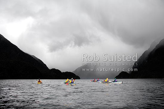 Wilderness sea kayaking trip in Doubtful Sound, Fiordland National Park. Sleet and rain storm approaching in background, Doubtful Sound, Fiordland, Southland District, Southland Region, New Zealand (NZ) stock photo.