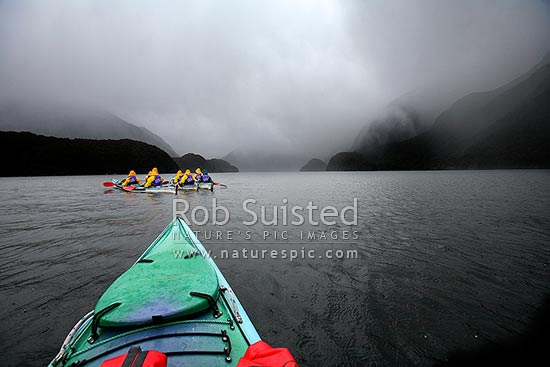 Wilderness sea kayaking trip in Doubtful Sound, Fiordland National Park. Sleet and rain storm starting, Doubtful Sound, Fiordland, Southland District, Southland Region, New Zealand (NZ) stock photo.