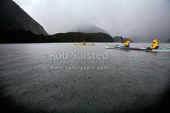 Wilderness sea kayaking trip in Doubtful Sound, Fiordland National Park, amongst a sleet, rain and hail storm, Doubtful Sound, Fiordland, Southland District, Southland Region, New Zealand (NZ) stock photo.
