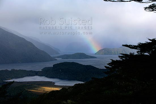 Moody rainbow over Hope Arm of Lake Manapouri, Fiordland National Park, Southland District, Southland Region, New Zealand (NZ) stock photo.