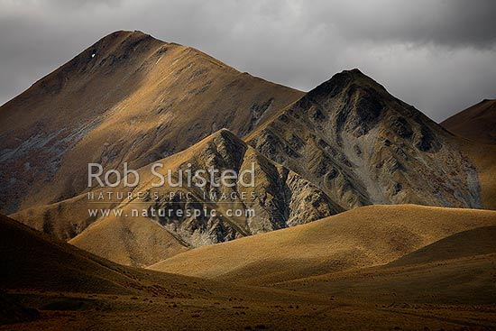 Light playing on the Lindis Pass tussock covered hills and valleys, Lindis Pass, Central Otago District, Otago Region, New Zealand (NZ) stock photo.