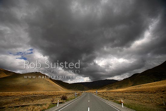 Dramatic heavy rain cloud over State Highway 8 (Lindis Pass - Tarras Road) as it winds into tussock covered hills and valley, Lindis Pass, Central Otago District, Otago Region, New Zealand (NZ) stock photo.
