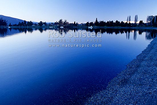 Calm winter reflections on Lake Te Anau. Boats moored. Snowy Murchison Mountains in distance., Te Anau, Southland District, Southland Region, New Zealand (NZ) stock photo.