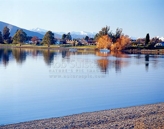 Calm winter reflections on Lake Te Anau and township, with snowy Murchison Mountains behind. Boats moored in distance, Te Anau, Southland District, Southland Region, New Zealand (NZ) stock photo.