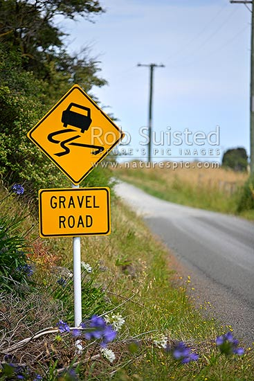 Gravel Road warning sign where tarseal road becomes an unsealed dirt road, New Zealand (NZ) stock photo.