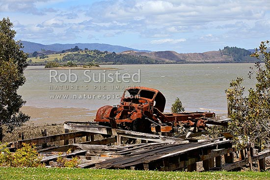 Old truck rusting away on old wharf on the Hokianga Harbour amongst Mangroves, Kohukohu, Hokianga, Far North District, Northland Region, New Zealand (NZ) stock photo.