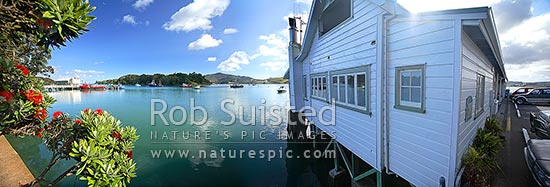 Mangonui harbour, wharf and historic building, with flowering pohutukawa flowers over water, Mangonui, Far North District, Northland Region, New Zealand (NZ) stock photo.