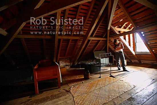 Woman tourist looking at Kerikeri Stone Store third floor attic interior, historic museum and period working store. 1832, New Zealand's oldest stone building, Kerikeri, Far North District, Northland Region, New Zealand (NZ) stock photo.