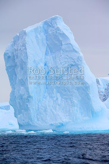 Leaning iceberg in an ice field. Glacial origin, Terre Adelie Land, Antarctica stock photo.