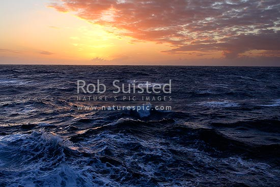 Southern ocean sea swell in front of a beautiful sunset. 58 degrees South, Southern Ocean, Antarctica stock photo.