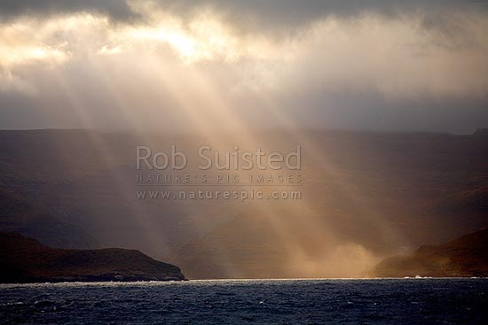 Shafts of sunlight hitting sea mist and spray above the main Auckland Islands inlets. World Heritage site, Auckland Islands, NZ Sub Antarctic District, NZ Sub Antarctic Region, New Zealand (NZ) stock photo.