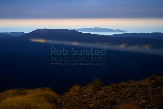 First shaft of morning sunlight under cloud onto Mount (Mt) Kapakapanui and forest covered ridges of the Tararua Ranges near Otaki Forks. Kapiti Island and cloud beyond, Tararua Forest Park, Kapiti Coast District, Wellington Region, New Zealand (NZ) stock photo.