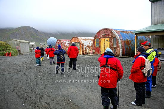 Tourist visitors to Macquarie Island ANARE science research station and buildings on the isthmus. Satellite communications dome behind, Macquarie Island, NZ Sub Antarctic District, NZ Sub Antarctic Region, Australia stock photo.