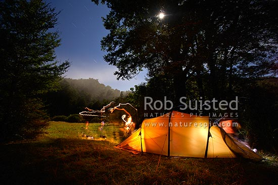 Moonlit campsite in beech forest clearing. Tramping campsite and tent lit with long exposure and tourches during full moon, Tararua Forest Park, Masterton District, Wellington Region, New Zealand (NZ) stock photo.
