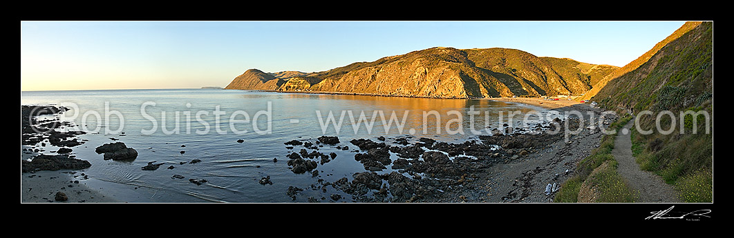 Image of Calm evening panoramic view of coastal settlement of Makara Beach and Ohariu Bay. Mana Island visible in distance, Makara Beach, Wellington City District, Wellington Region, New Zealand (NZ) stock photo image