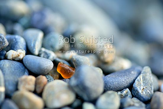 Nature's own glass recycling plant - beach gravels and pebbles slowly grinding glass back into silica sand from which is is derived. Brown glass. rubbish, New Zealand (NZ) stock photo.