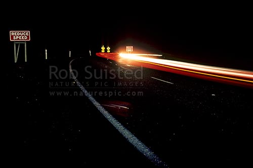 Car headlights winding along Desert road at night, Desert Road, Taupo District, Waikato Region, New Zealand (NZ) stock photo.