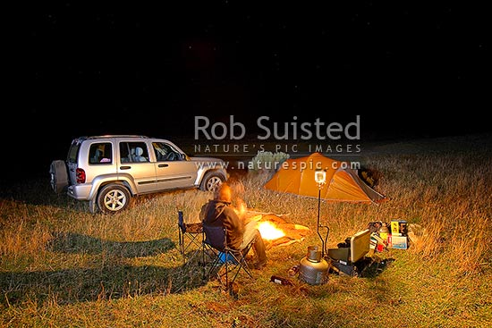 4x4 tent camping at the coast. 4wd and camper with fire, lantern, and cooking equipment at night with stars above, Wairarapa, South Wairarapa District, Wellington Region, New Zealand (NZ) stock photo.