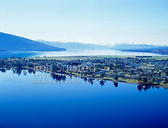 Aerial view over a smooth calm Lake Te Anau and Te Anau township on delta. Snowy Fiordland National Park mountains behind, Te Anau, Southland District, Southland Region, New Zealand (NZ) stock photo.