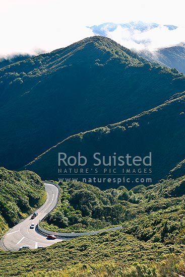 Cars on the Remutaka (Rimutaka) Hill Road climbing to the 555m summit linkng Wellington and the Wairarapa. Tararua Range beyond. (State Highway 2), Remutaka, Upper Hutt City District, Wellington Region, New Zealand (NZ) stock photo.
