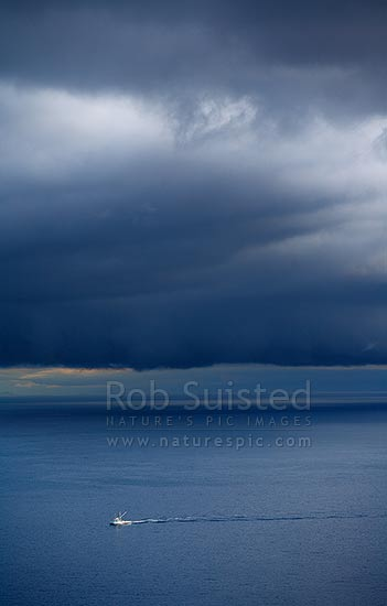 Running home before the storm. Fishing boat returning to port as a dramatic southerly weather front looms over Cook Strait. South Island under cloud, Wellington, Wellington City District, Wellington Region, New Zealand (NZ) stock photo.