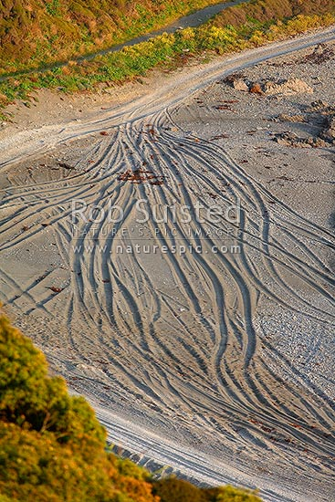 4x4 tracks criss crossing across a sandy beach, looking like arteries or viens, 4WD, New Zealand (NZ) stock photo.
