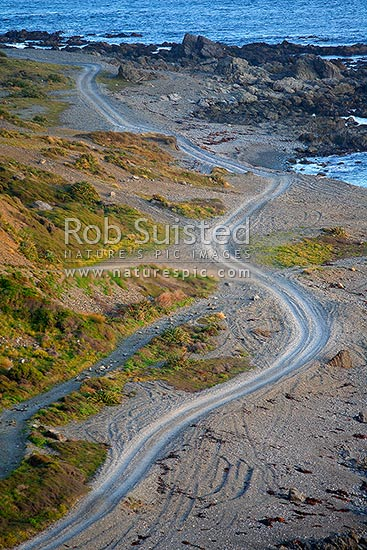 A 4x4 gravel road snaking and twisting along the coastal foreshore of the Wellington South Coast, Wellington, Wellington City District, Wellington Region, New Zealand (NZ) stock photo.