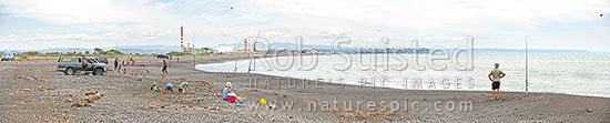 Panorama of families picnicking and recreational fishing on Napier foreshore near the Tukituki, Ngaruroro and Clive River mouths. Christmas Day. Awatoto fertiliser plant behind, Clive, Napier City District, Hawke's Bay Region, New Zealand (NZ) stock photo.