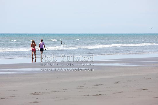Two young woman walking on beach, Peka Peka Beach, Kapiti Coast District, Wellington Region, New Zealand (NZ) stock photo.