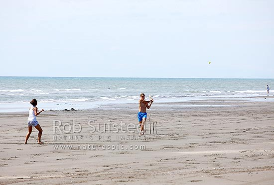 Young couple playing cricket on the beach during summer holidays, Peka Peka Beach, Kapiti Coast District, Wellington Region, New Zealand (NZ) stock photo.