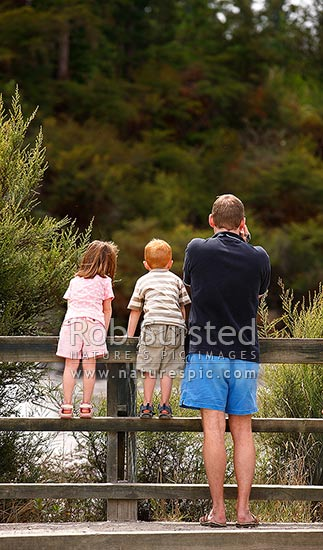 Father and his kids looking over railings at geothermal mudpools. Dad filming and boy and girl watching, Rotorua, Rotorua District, Bay of Plenty Region, New Zealand (NZ) stock photo.
