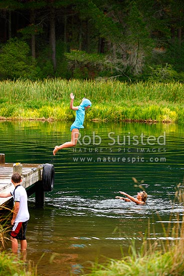 Family enjoying swimming, jumping and diving from jetty on the Waikato River. I can fly! Summertime, Mihi, Rotorua, Rotorua District, Bay of Plenty Region, New Zealand (NZ) stock photo.